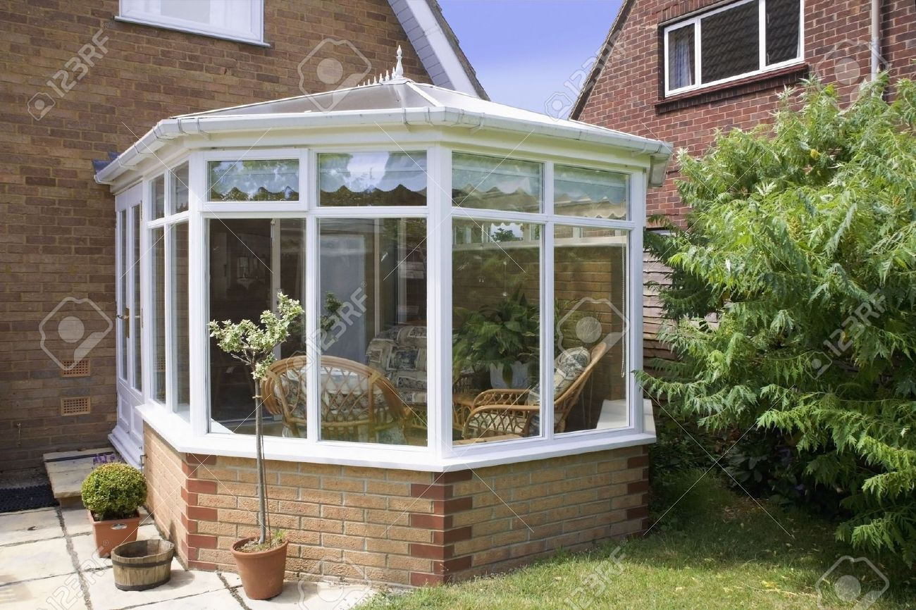 2111385 conservatory tables chairs plants room in house next to garden Stock Photo Conservatories  & Orangeries